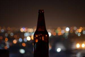 Bottle of home brewed beer city lights behind