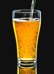 Clear Home Brewed Beer Being Poured into a beer glass