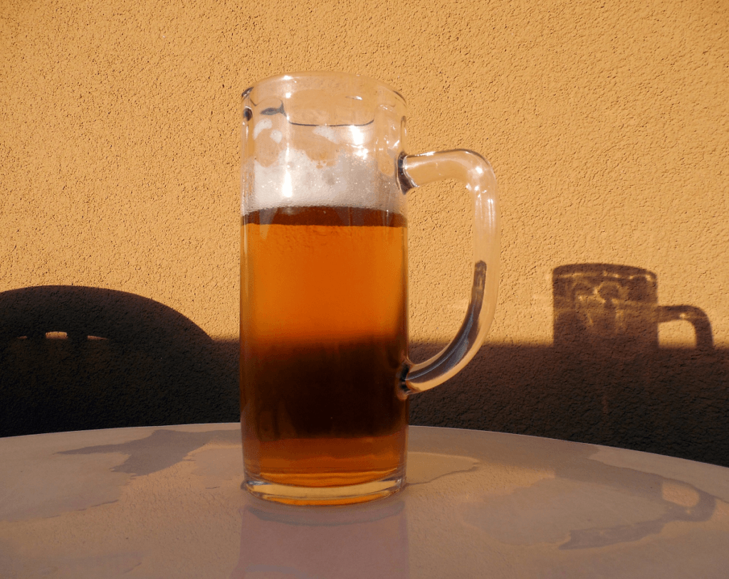 Homebrew beer sitting on a table with shadow behind it